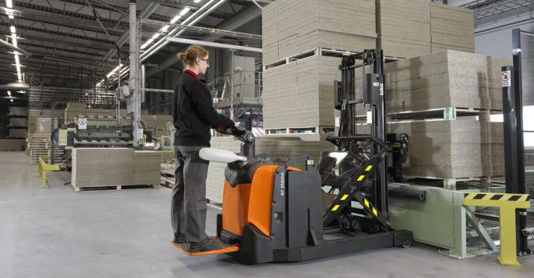 A flexible stacker with retractable mast in warehouse