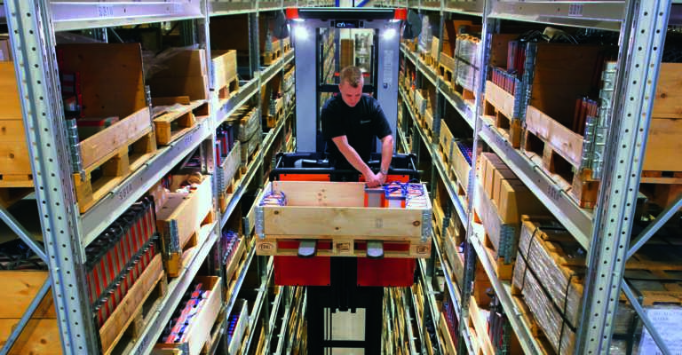 Man doing high-level order picking in narrow aisle