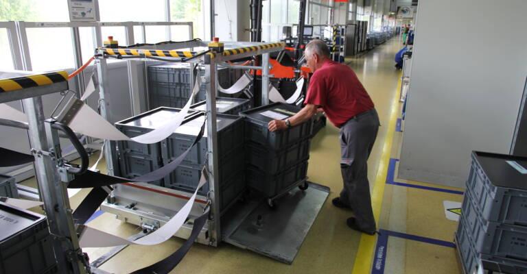 Pracovník nakládá materiál do automatického tahače
