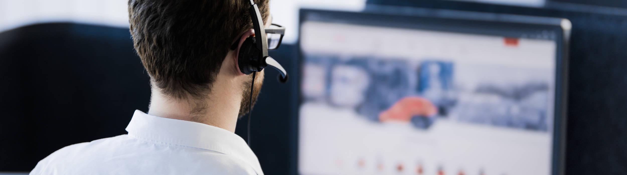 Pracovník IT sedí u stolního počítače se sluchátky na uších