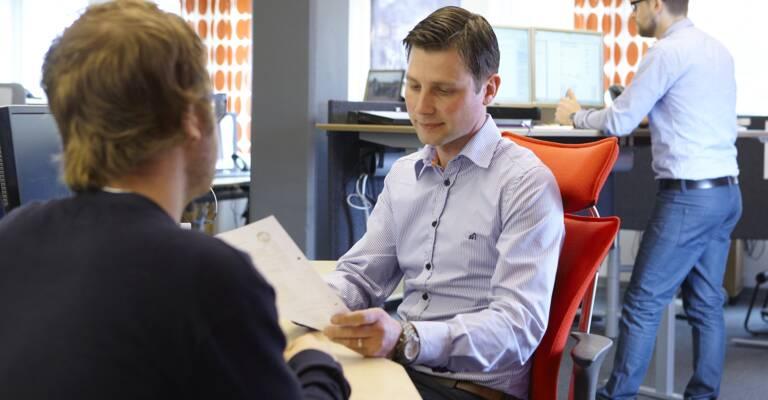 To mænd sidder ved et bord på et kontor