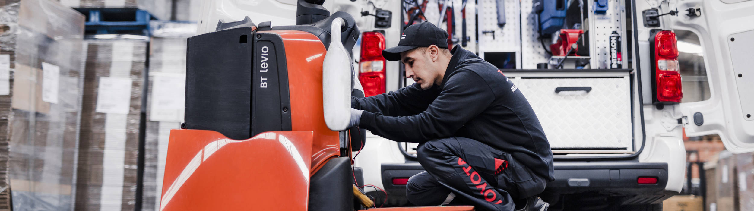 Toyota service technician maintaing a powered pallet truck