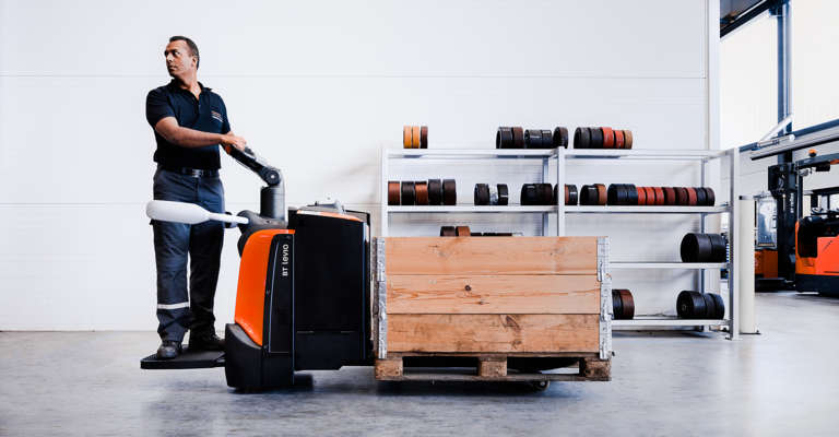 Man driving a platform powered pallet truck