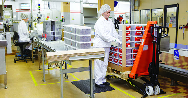 Woman packing goods on hand pallet truck
