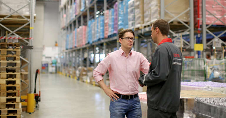 Two men standing in warehouse talking