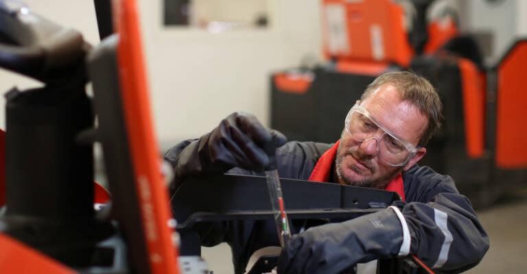 Técnico de mantenimiento arreglando una carretilla