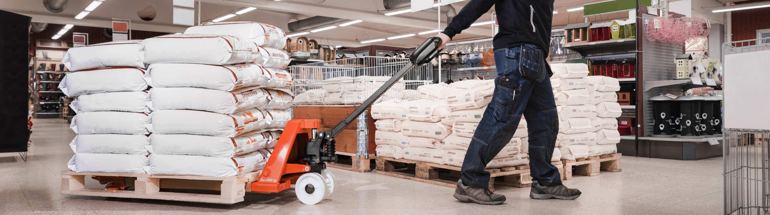 transpaleta manual moviendo mercancías en un supermercado
