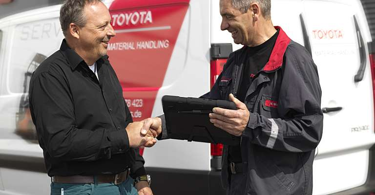Two men talking in front of a service van