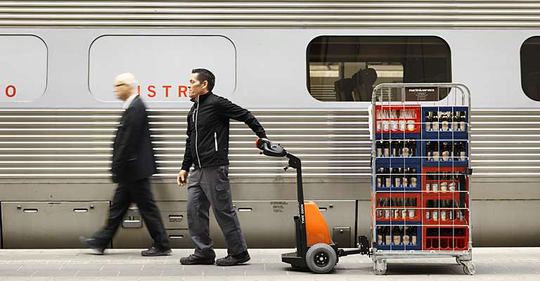 Man using a pedestrian tow tractor on train station
