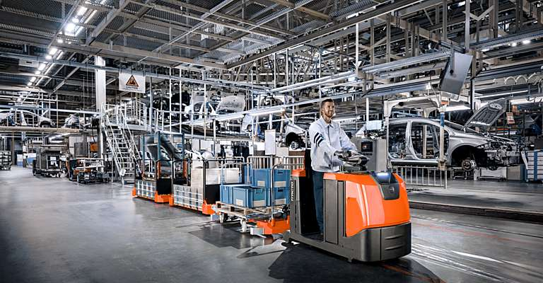 Tauetraktor transporterer deler i bilfabrikk
